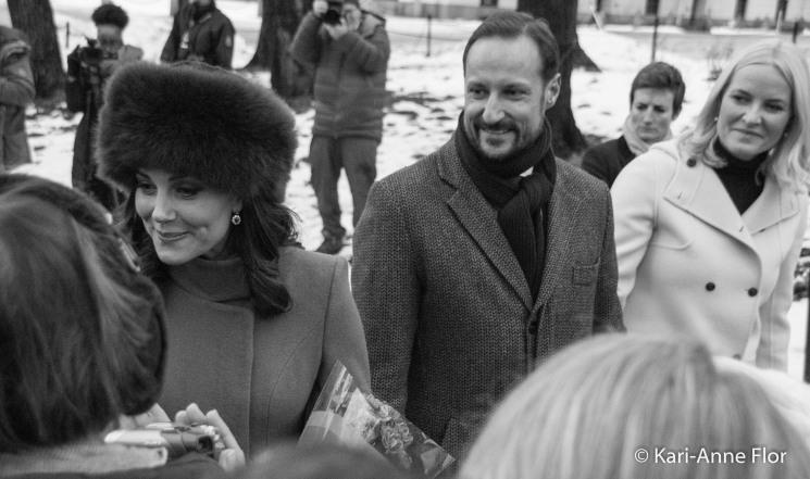 Hertuginne Kate snakker med folk, med kronprinsparet som tilskuere i bakgrunnen.
