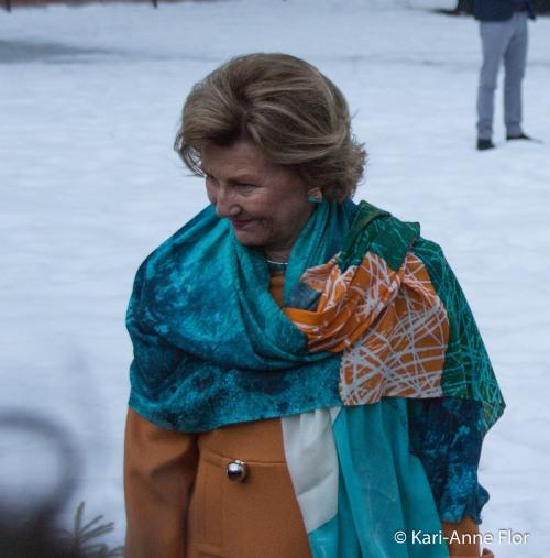 Dronning Sonja i turkist og gult antrekk ute i slottsparken.