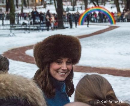 Hertuginne Kate i brun pelslue med regnbuen i bakgrunnen.