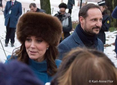 Hertuginne Kate i brun pelslue. Kronprins Haakon i bakgrunnen.